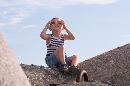Dreamy little boy in sunglasses and sailor shirt looking at the sky sitting on concrete breakwater Imagens