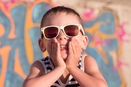 boca cerrada: smiling little boy wearing sunglasses and striped shirt closed his mouth with hands on graffiti background