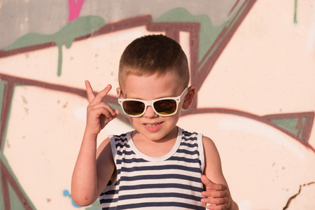 smiling little boy wearing trendy sunglasses and striped shirt on graffiti background lifted two fingers up