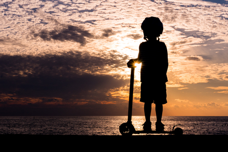 the magnificent: Silhouette of a little boy wearing helmet standing on scooter against the background of a sea sunset