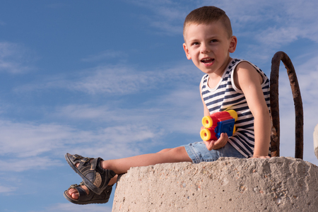 adorable small boy in vest and sandals with binoculars sitting on breakwater on the blue sky background Foto de archivo