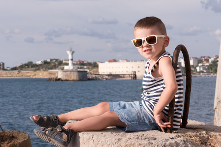 funny little boy in sunglasses and sailor stripes vest sitting on concrete breakwater with sea and shore with lighthouse background