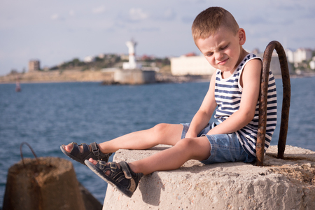 funny little boy wearing sailor stripes singlet and shorts with sandals with a grimace on his face and eyes closed against the sea bay with lighthouse in summer