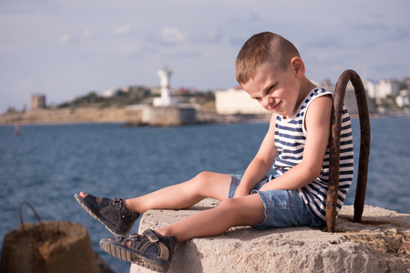funny little boy wearing sailor stripes singlet and shorts with sandals with a grimace on his face against the sea coast with lighthouse in summer