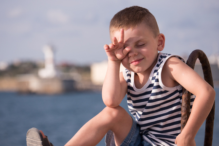 Cool little boy in singlet and shorts closed his eyes from the sun with his hand on the background of the sea and shore in hot summer