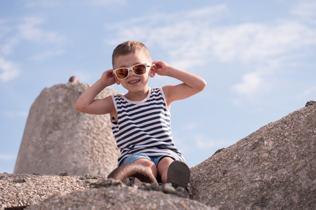 Cute smiling little boy in white sunglasses and sailor stripes vest sitting on a concrete breakwater on blue sky background