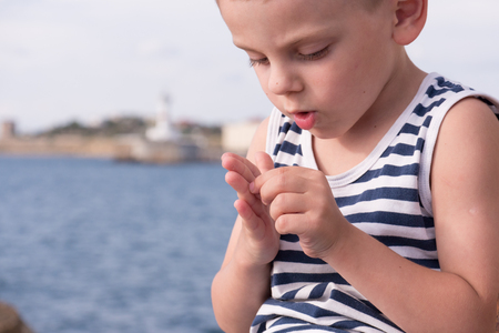 Attentive little boy wearing sailor stripes shirt gets a splinter from his finger