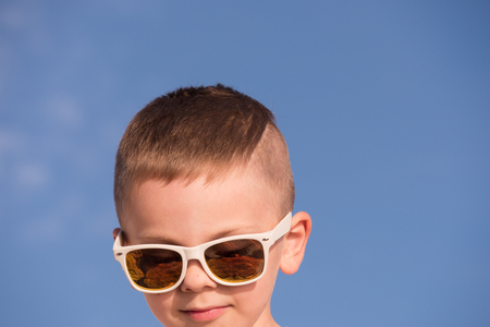 cute little boy wearing sunglasses on blue sky background with trendy cropping Stock Photo