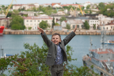 gladness: Happy handsome little boy in a jacket raised his hands up in sea port