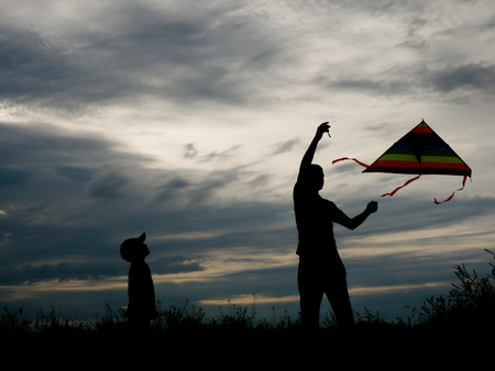 father and son flying a kite on the background of beautiful sunset