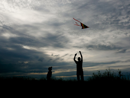 father and son flying a kite at sunset