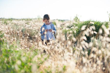 friendless: Pensive little boy wearing shirt standing in field amongst plants