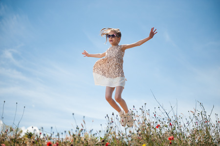 happy beautiful little girl wearing sunglasses and dress jumping outdoors among plants on sky background