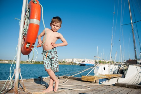 funny little healthy boy in shorts stands on the pier with sea and blue sky background Stock Photo