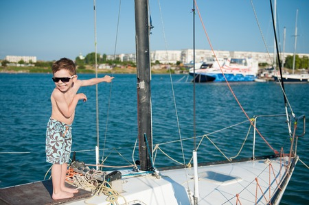82245641 - Niño feliz usando pantalones cortos y gafas de sol a bordo del  yate de lujo 8a20d1ad19b