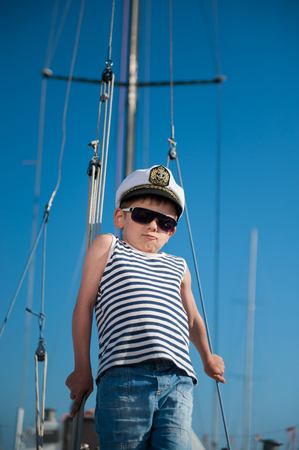 cool handsome little kid captain aboard luxury yacht