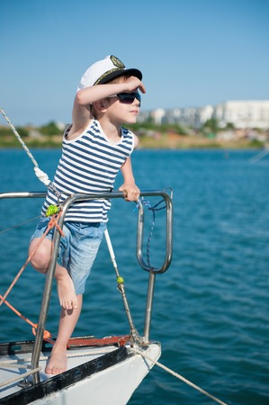 cute little captain kid wearing captain hat and trendy sunglasses peering into the distance standing aboard luxury boat
