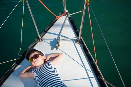 82661764 - Feliz pequeño capitán niño acostado con placer a bordo de su  barco de lujo 820266fbbba