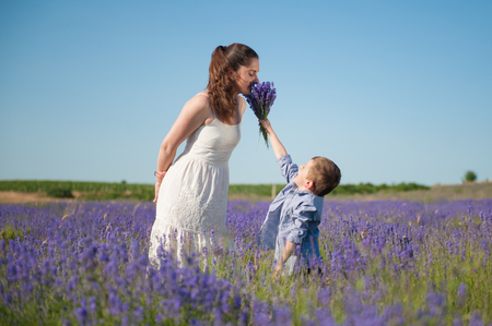 Happy little son gives mother to smell the flavor of a bouquet of flowers Reklamní fotografie - 83030651