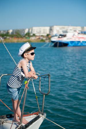 cool cute little boy captain wearing sunglasses aboard luxury boat