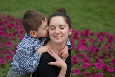 Little boy kissing and embracing his happy mother Stock Photo