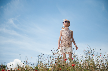 cute little girl in fashion dress and sunglasses standing among the field of flowers and grass on the background of blue cloudy sky