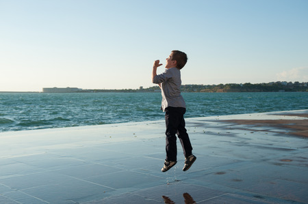 cheerful little boy jumping on the background of sea port at sunset