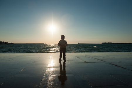 one little boy watching the sea against the sunset Stock Photo