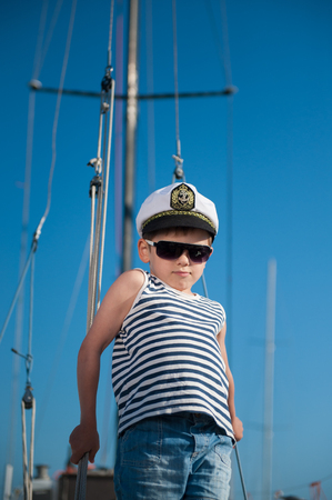 happy little boy wearing captain hat and sailor striped shirt aboard recreational boat in summer sunny day