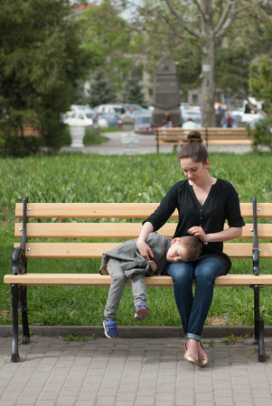 tenderly: mother sitting on the bench tenderly embracing her son lying on her hips