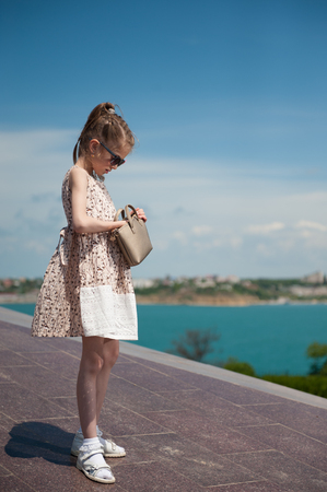 trendy little girl wearing dress and sunglasses looking for something in her pouch on sky and sea background
