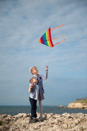 brother and sister hold flying kite while standing on a cliff against the sea Stock Photo