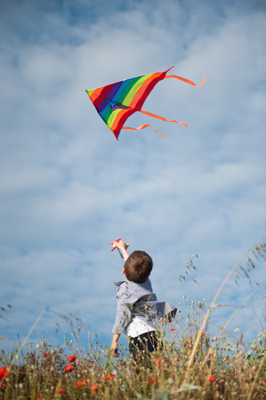 little boy in a shirt holding colorful kite flying in the air