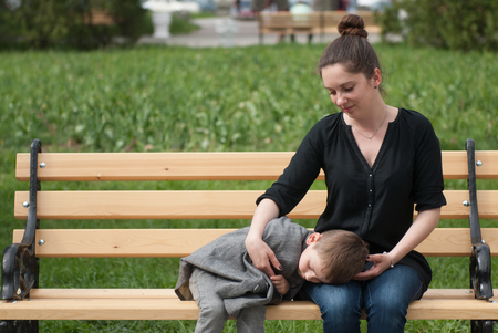 tenderly: mother sitting on the bench gently embracing her small son sleeping on her hips holding tenderly her finger Stock Photo