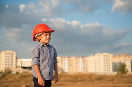 gewerkschaft: cute kid wearing builder helmet on the new buildings background