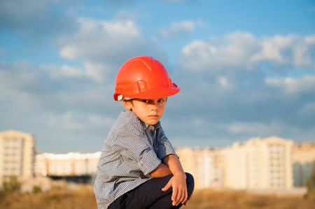 gewerkschaft: cute serious little boy wearing orange helmet sitting on the new buildings and beautiful sky background at warm sunset Lizenzfreie Bilder
