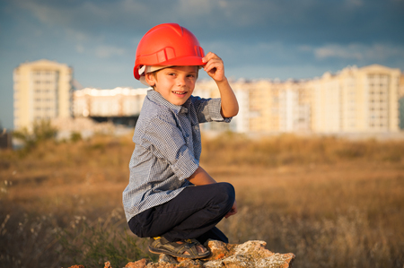 handsome little boy wearing orange helmet sitting on the new buildings background at warm sunset Stock Photo