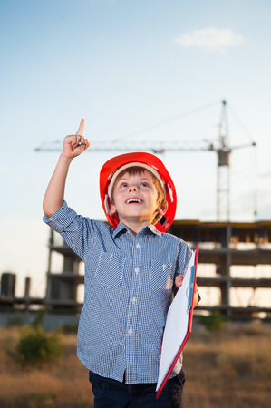tough: happy cute little kid builder in a helmet found a solution standing on construction site with tower crane