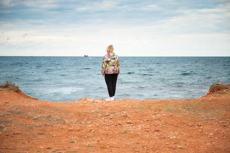 soltería: sola mujer adulta que mira en el mar en tiempo ventoso del otoño