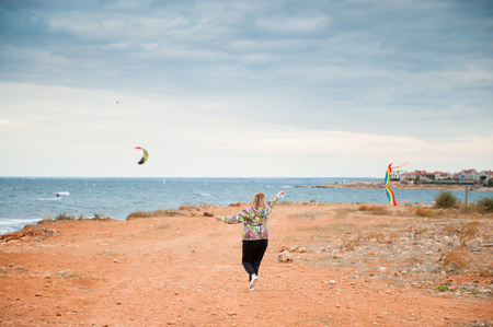 aging woman: adult female playing kite running on the ground by the sea in overcast autumn weather