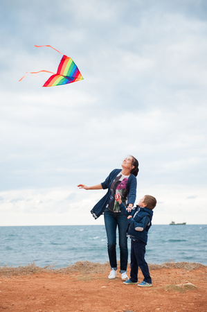 beautiful mother and child playing with a kite on the sea coast in the cloudy weather