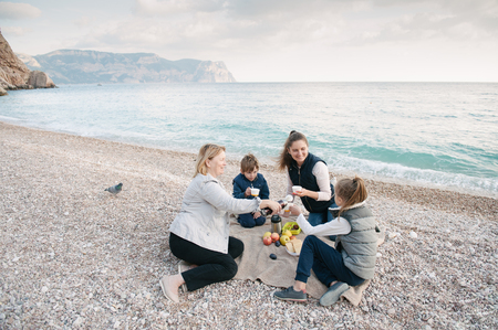three generations: happy family consisting of grandmother, mother and two kids on a picnic by the sea in cold weather Stock Photo