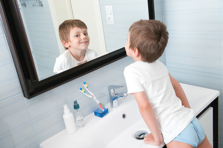 happy smiling little kid in blue bathroom looking at himself in the mirror