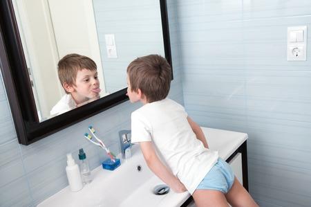 욕실 거울에 자신의 혀를 보여주는 재미있는 작은 소년 스톡 콘텐츠