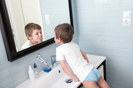 funny small boy showing his tongue out in the bathroom mirror Stok Fotoğraf
