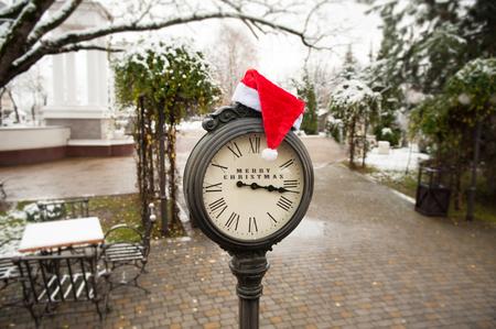 numeros romanos: stylish vintage clock with santa hat and the words Merry Christmas Foto de archivo