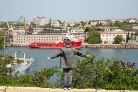 small boy in a jacket stands against the backdrop of a sea port, placing his hands in the sides imitating a flight