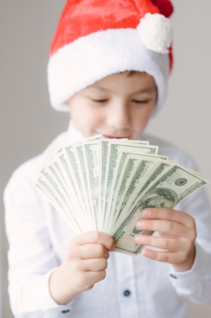 happy cute boy in Santa hat holding wad of hundred dollar banknotes