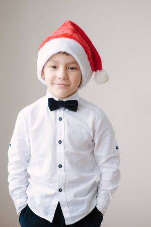 Beautiful boy in santa hat and bow tie smiling with his hands in his pockets Stok Fotoğraf