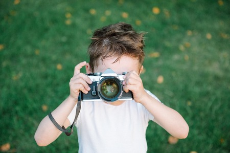 funny cute kid wants to take a picture with his vintage film camera on green grass backdrop with some fallen leaves Stock Photo
